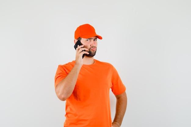 주황색 티셔츠, 모자를 쓰고 생각에 잠긴 표정으로 휴대폰 통화를 하는 배달원. 전면보기.