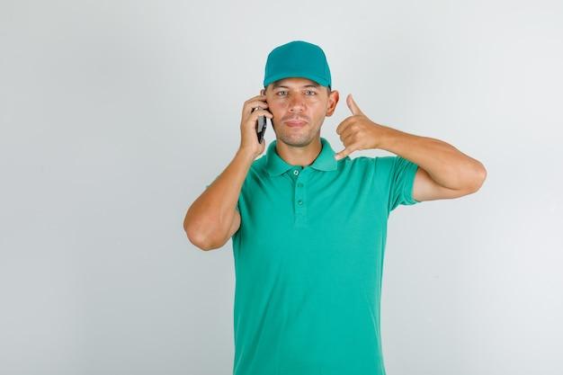 Uomo di consegna parla al telefono con il pollice in su in maglietta verde con cappuccio