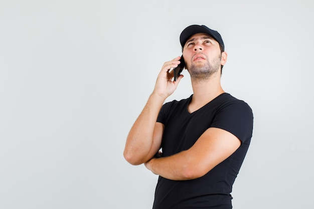 Delivery man talking on smartphone in black t-shirt