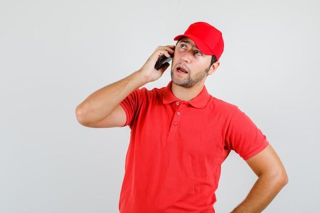 Uomo di consegna che parla sullo smartphone in maglietta rossa