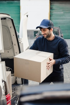 Delivery man unloading cardboard box from vehicle