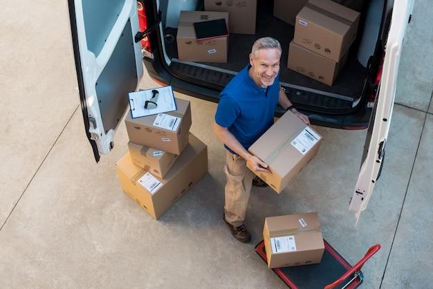 Delivery man unloading parcel