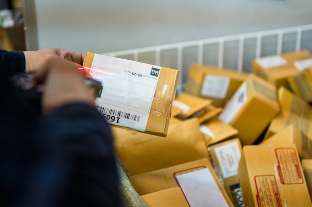 Доставщик, использующий лазерный сканер, сканирующий картонную коробку посылки на распределительном складе
