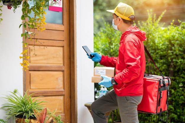 Доставщик в синих перчатках и красной куртке ищет адрес клиента по мобильному телефону