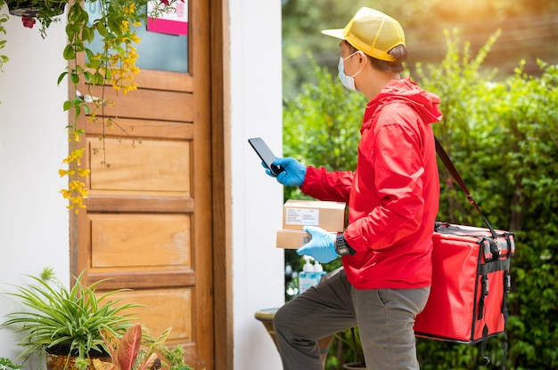 Delivery man wearing blue gloves and red jacket, searching for customer address by mobile phone