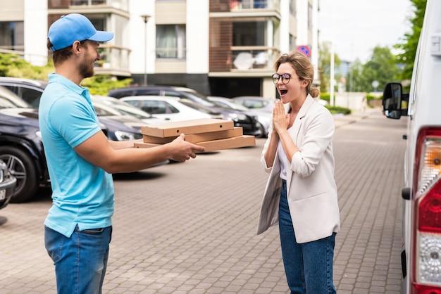 파란색 유니폼을 입은 배달원은 여성에게 피자를 배달합니다.