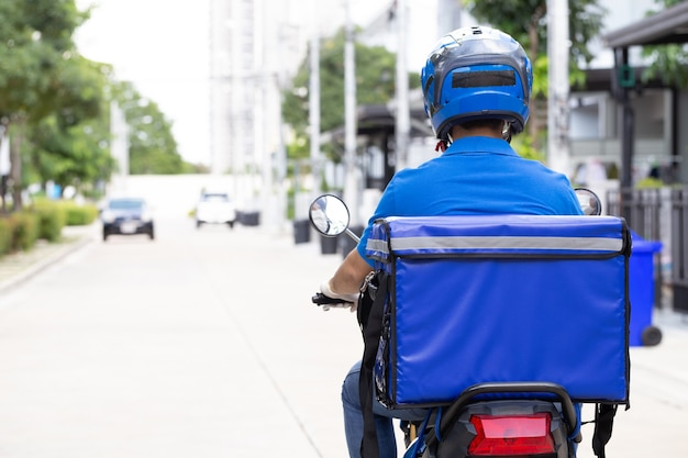 파란색 유니폼 타고 오토바이 및 배달 상자를 입고 배달 남자