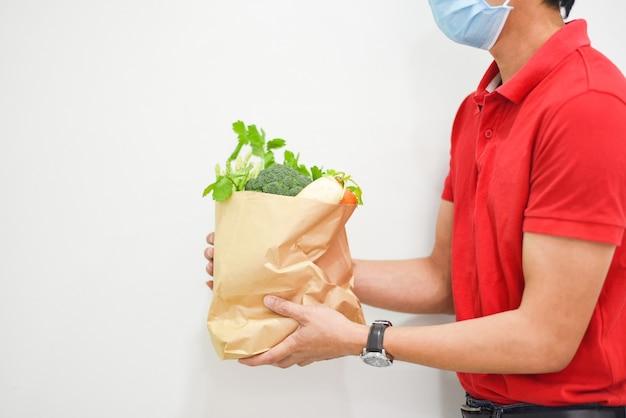 Доставщик в маске для лица и рука, держащая упаковку для пищевых продуктов служба доставки еды на дом