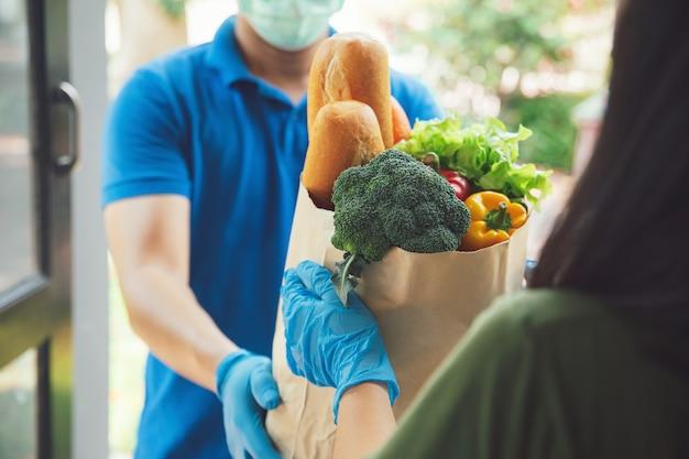 食品の青いユニフォームハンドリングバッグにフェイスマスクと衛生用手袋を着用して配達人