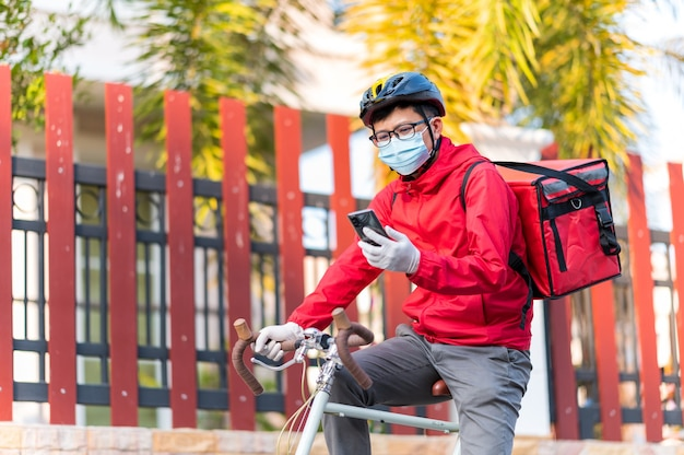 Delivery man wearing face protective mask to avoid corona virus look at the phone to find the customer address through the application.