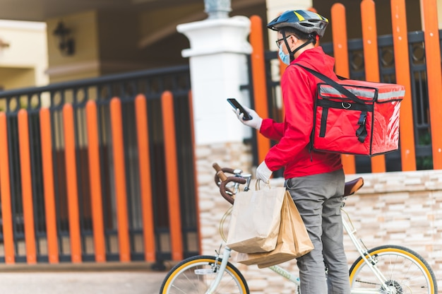 Delivery man wearing face protective mask to avoid corona virus red uniform cycling to deliver products to customers at home.