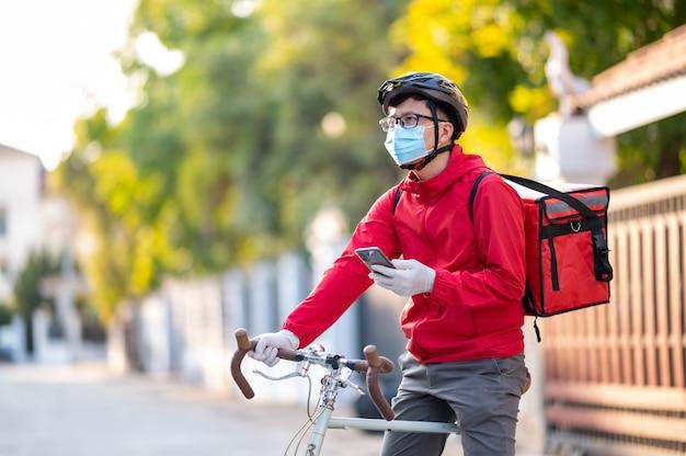 코로나 바이러스를 피하기 위해 안면 보호 마스크를 쓴 배달원은 애플리케이션을 통해 고객 주소를 찾기 위해 전화를 봅니다.