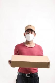 Доставка человек в медицинской маске и коробке в руках. курьером. доставка на дом. карантинный герой.