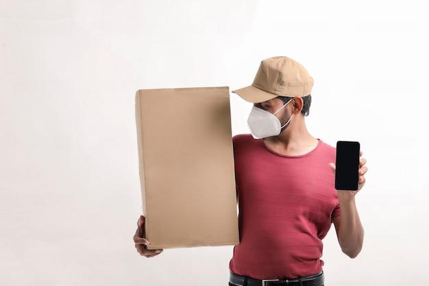 의료용 마스크를 쓰고 손에 상자가 있는 스마트폰 화면을 보여주는 배달원. 택배. 온라인 기술을 주문하십시오.