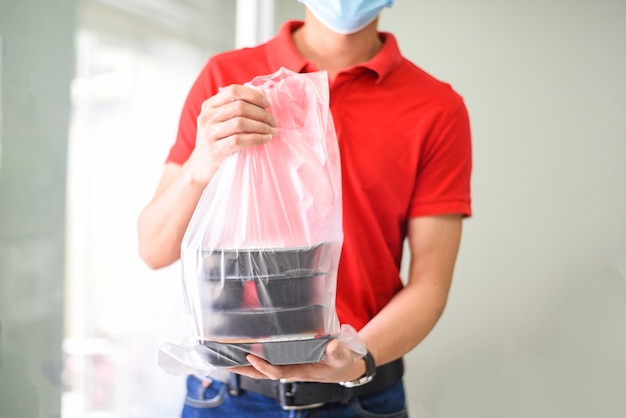 Доставщик в защитной маске от коронавируса и рука, держащая упаковку для пищевых продуктов