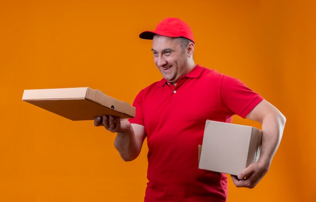 Работник службы доставки, одетый в красную форму и кепку, держит пакет с коробкой для пиццы и улыбается клиенту, жизнерадостно улыбаясь оранжевой стене