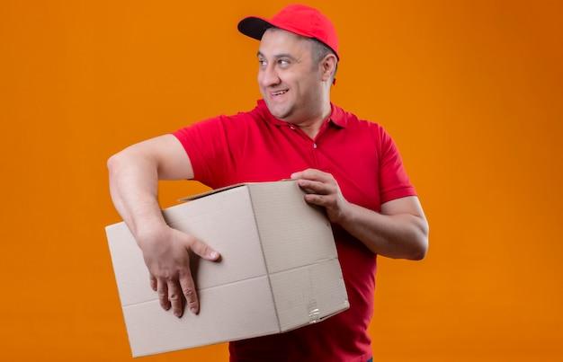赤い制服と分離のオレンジ色の壁に笑みを浮かべてよそ見大きな段ボール箱を保持しているキャップを身に着けている配達人