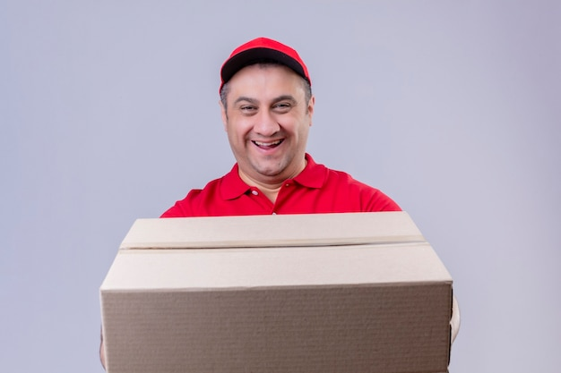 赤い制服を着た配達人と孤立した白いスペースの上に立って幸せそうな顔でフレンドリーな笑顔の大きな段ボール箱を保持しているキャップ