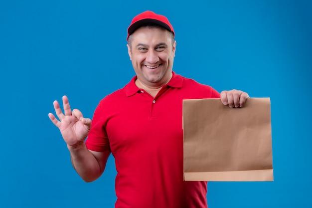 빨간색 유니폼과 모자를 입고 배달 남자 긍정적이고 행복 찾고 파란색 격리 된 공간 위에 서있는 확인 서명을 찾고