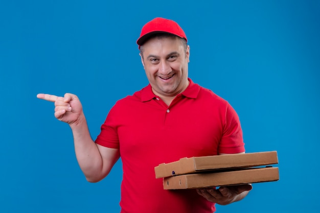 Доставщик в красной форме и кепке держит коробки для пиццы, улыбаясь счастливым лицом, указывая указательным пальцем в сторону, стоя над синим пространством
