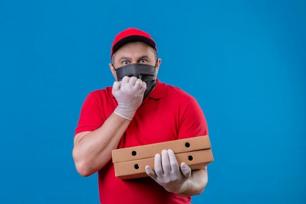 Доставщик в красной униформе и кепке в защитной маске держит коробки с пиццей в напряжении и нервозности, держа руку на рту, кусая ногти, стоя над синим пространством