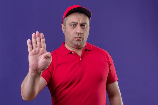 Доставка человек в красной форме и кепке с открытой рукой, делая остановки жест, хмурясь, стоя над фиолетовой стеной