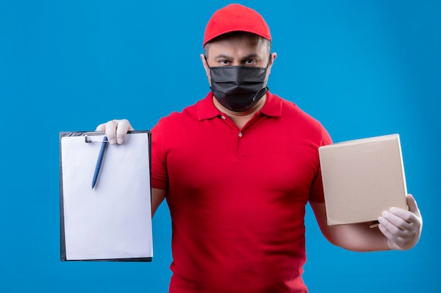 Uomo di consegna che indossa divisa rossa e cappuccio in maschera protettiva per il viso tenendo la scatola di cartone e appunti con spazi vuoti cercando ta fotocamera con grave faccia accigliata in piedi su backg blu