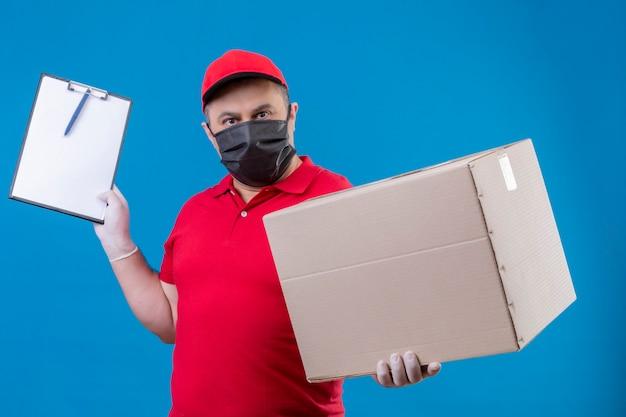 Uomo di consegna che indossa uniforme rossa e berretto in maschera protettiva facciale che tiene grande scatola di cartone e appunti con faccia seria in piedi sopra lo spazio blu