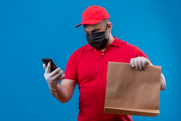 Delivery man wearing red uniform and cap in facial protective mask holding paper package and looking at screen of his mobile phone with serious face standing over blue space