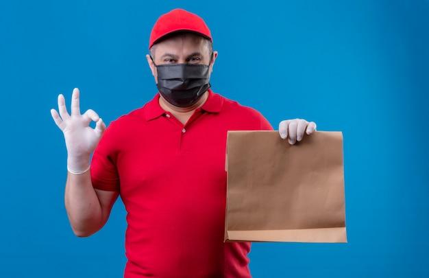 Uomo di consegna che indossa l'uniforme rossa e il cappuccio nella maschera protettiva facciale che tiene il pacchetto di carta positivo e felice che fa segno giusto che sta sopra lo spazio blu