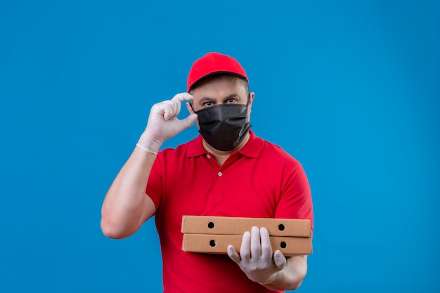 Delivery man wearing red uniform and cap in facial protective mask holding pizza boxes gesturing with hand showing small size sign, measure symbol over isolated blue wall
