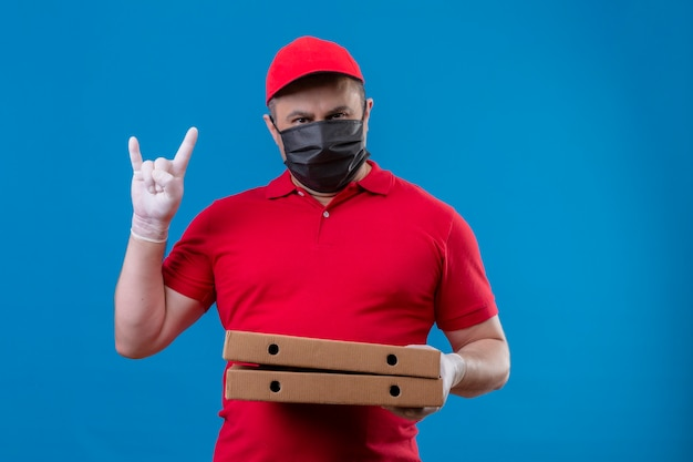 Delivery man wearing red uniform and cap in facial protective mask holding pizza boxes making rock symbol with serious face standing over blue space