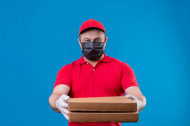 Delivery man wearing red uniform and cap in facial protective mask holding pizza boxes stretching out to camera looking confident standing over blue space