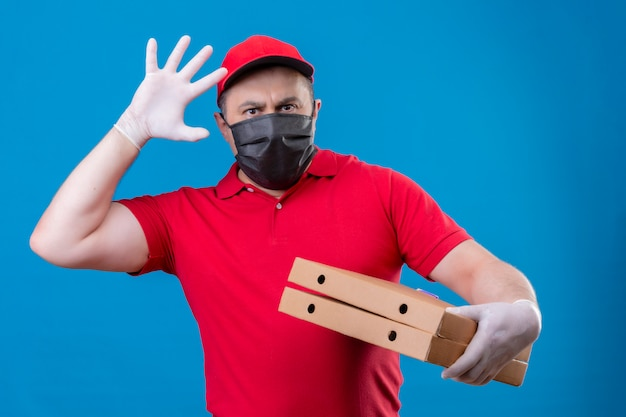 Delivery man wearing red uniform and cap in facial protective mask holding pizza boxes with raised hand and palm with angry expression standing over isol