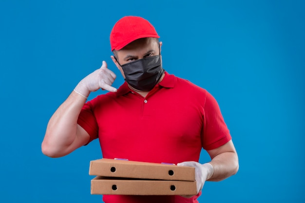 Delivery man wearing red uniform and cap in facial protective mask making call me gesture with hand holding pizza boxes over blue wall