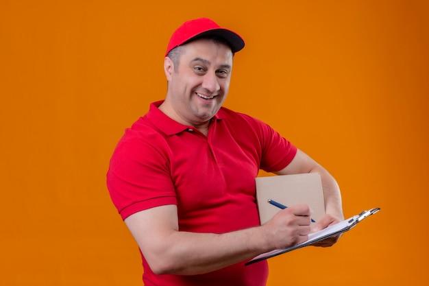 Fattorino che indossa il pacchetto e la lavagna per appunti della scatola della tenuta del cappuccio e dell'uniforme rossa con la penna che sorride allegramente sopra la parete arancio isolata