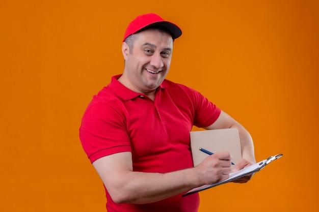 Uomo di consegna che indossa l'uniforme rossa e il pacchetto della scatola della tenuta del cappuccio e appunti con la penna che sorride allegramente in piedi spazio