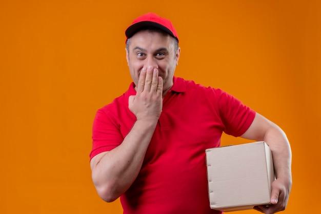 Uomo di consegna che indossa l'uniforme rossa e il pacchetto della scatola della tenuta del cappuccio che sembra sorpreso che copre la bocca con lo spazio della mano