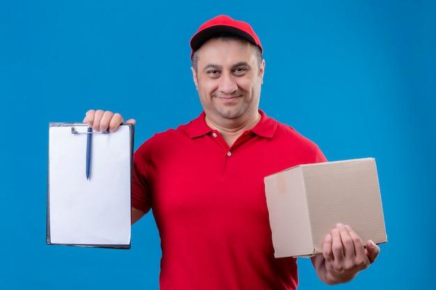 Uomo di consegna che indossa l'uniforme rossa e cappuccio che tiene la scatola di cartone che mostra appunti con gli spazi vuoti che sembrano sorridere fiducioso in piedi sopra lo spazio blu