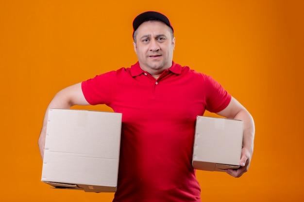 Fattorino che indossa l'uniforme rossa e cappuccio che tengono le scatole di cartone che sembrano sovraccariche e stanche sopra la parete arancio