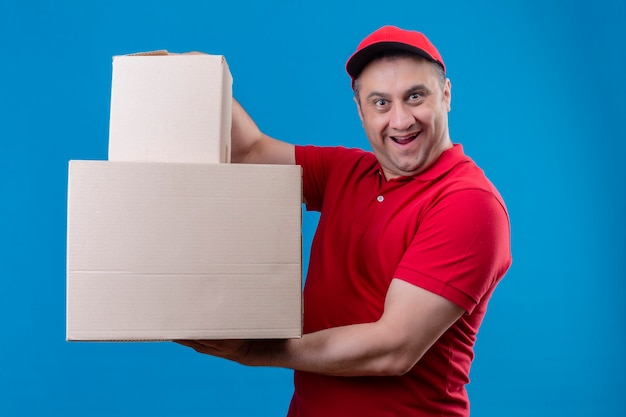 Delivery man wearing red uniform and cap holding cardboard boxes smiling looking exited and surprised standing over blue space