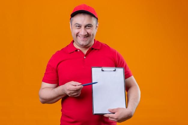 Fattorino che indossa la lavagna per appunti della tenuta del cappuccio e dell'uniforme rossa che indica con la penna che sembra sorridere positivo e felice sopra la parete arancio