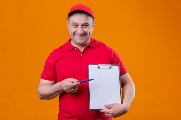 Uomo di consegna che indossa l'uniforme rossa e la lavagna per appunti della tenuta del cappuccio che indica con la penna che sembra in piedi sorridente positiva e felice
