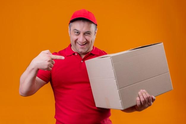 Uomo di consegna che indossa l'uniforme rossa e cappuccio che tiene grande scatola di cartone che punta con il dito indice ad esso sorridente in piedi sicuro