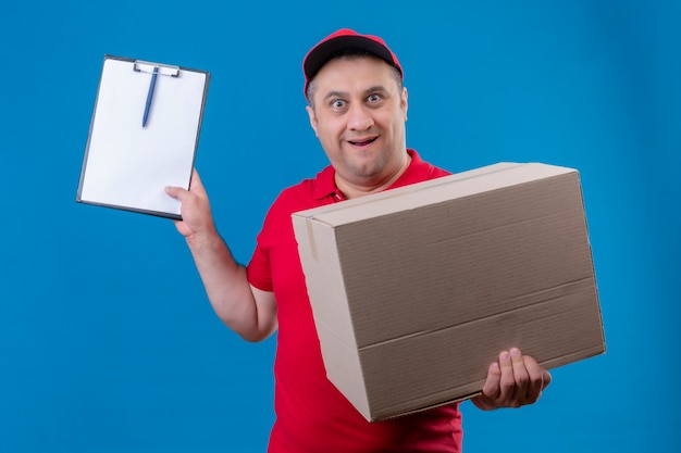Delivery man wearing red uniform and cap holding large cardboard box showing clipboard looking surprised standing over isolated blue space