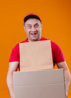 Uomo di consegna che indossa l'uniforme rossa e cappuccio che tiene il pacchetto di carta e le scatole per pizza che sembrano sorpresi e felici