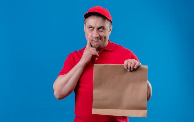 Uomo di consegna che indossa l'uniforme rossa e cappuccio che tiene il pacchetto di carta che tocca il mento alzando lo sguardo e pensando con espressione pensierosa in piedi sopra lo spazio blu