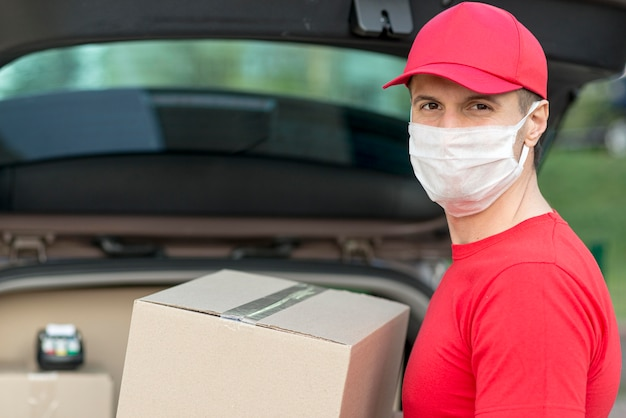 Uomo di consegna che indossa una maschera chirurgica