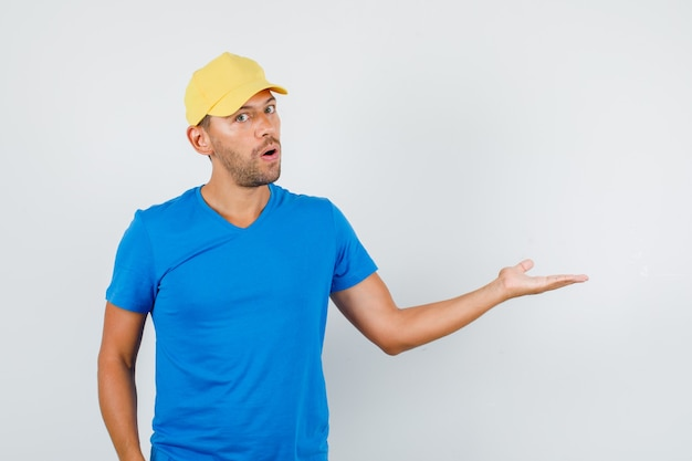 Delivery man welcoming or showing something in blue t-shirt