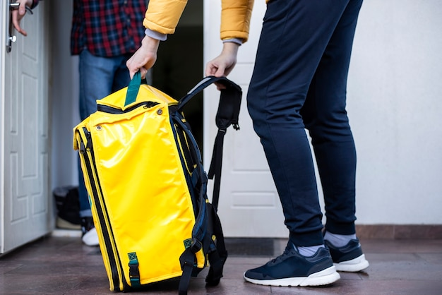 Delivery man at winter taking off yellow backpack and client standing in the doorway